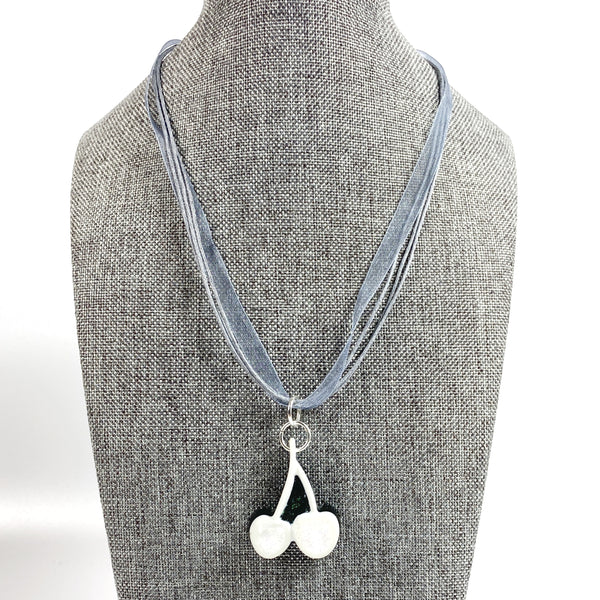 Iridescent White Cherries on Black Resin, Grey Necklace on grey tweed necklace stand