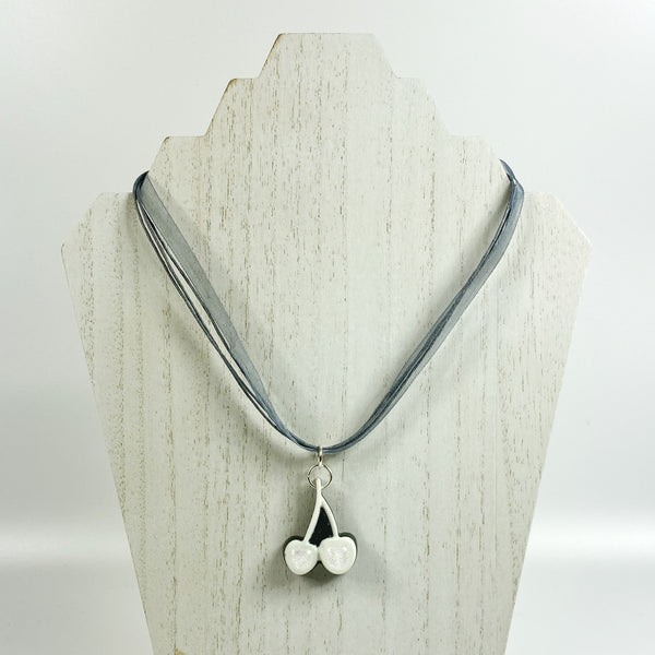 Iridescent White Cherries on Black Resin, Grey Necklace  on pale wood necklace stand