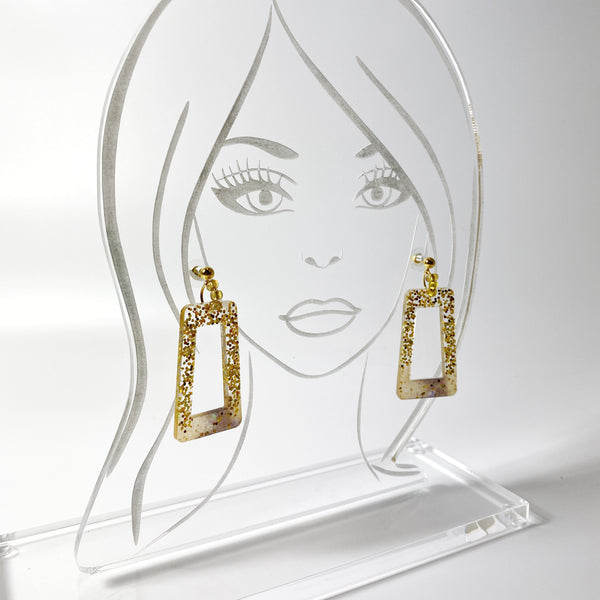 Squared gold glitter hoops on acrylic display head
