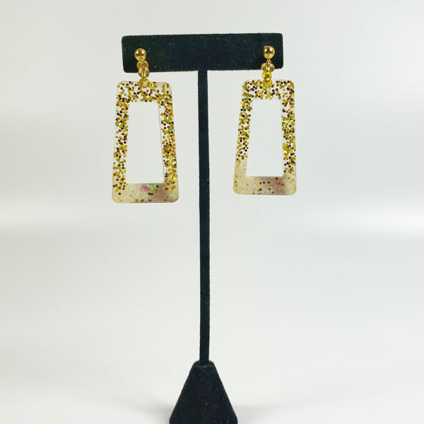 Squared gold glitter hoops on black display stand