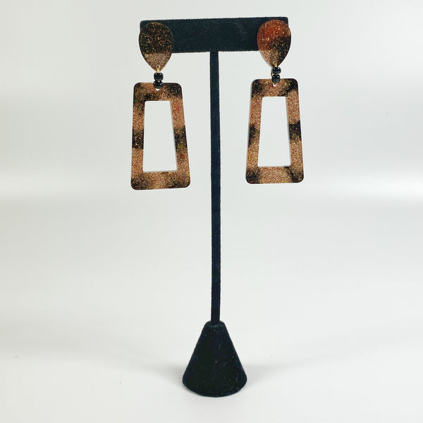 Brown and Black Striped Square Hoop Resin Earrings on black earring stand
