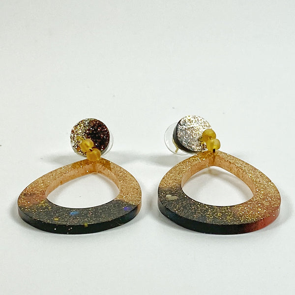 Teardrop shaped resin hoop earrings in brown fading to gold, side view