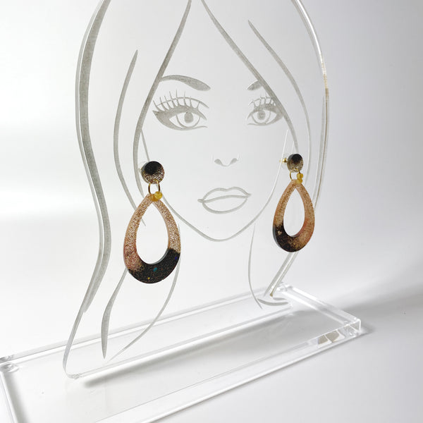 Teardrop shaped resin hoop earrings in brown fading to gold on acrylic display stand