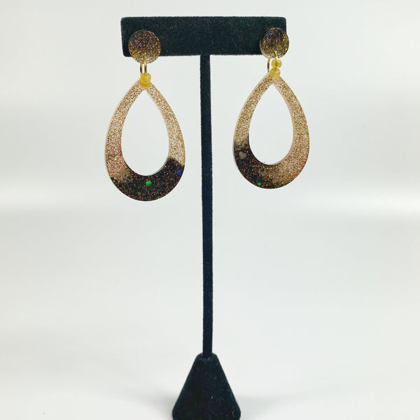 Teardrop shaped resin hoop earrings in brown fading to gold on black earring stand