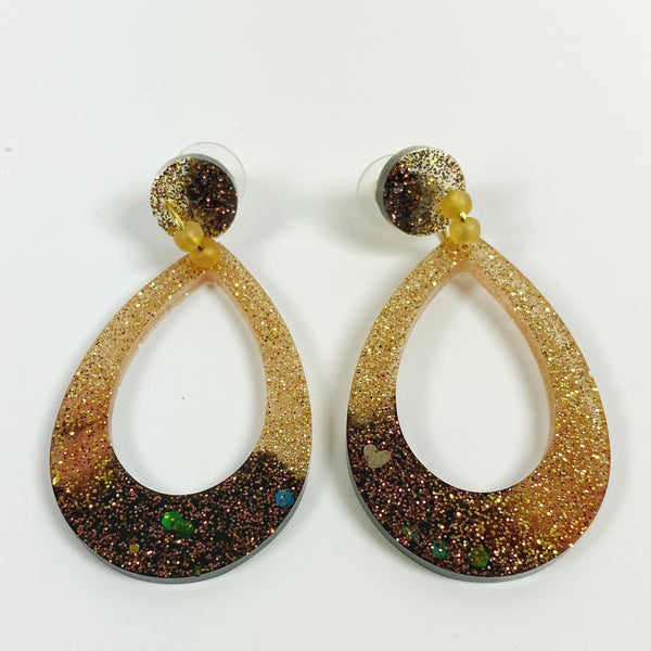Teardrop shaped resin hoop earrings in brown fading to gold, front view