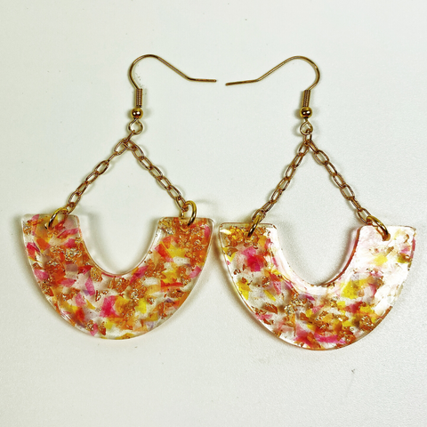 Clear resin earrings with red and gold inclusions resembling sangria, hung from an earwire by a chain