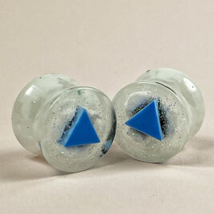 front side of gauges showing a crisp blue triangle in sparkly clouds of white and silver