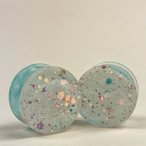 Gauge front: Milky white with glitter in gold and blue