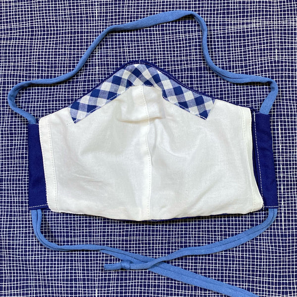 inside of solid navy face mask, white cotton fabric with. navy gingham nose wire channel
