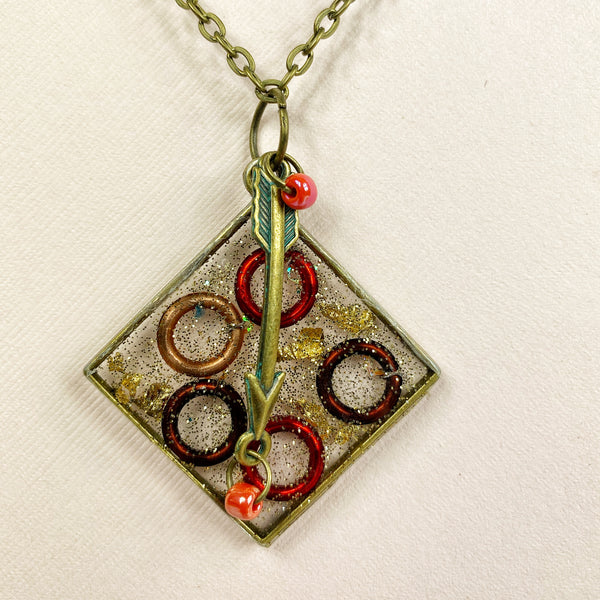 In this closeup of the necklace, you see the arrow charm, red glass beads, and the vibrant red and rust colors of the target circles