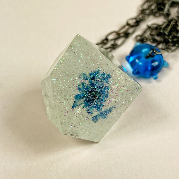 Close up of necklace showing blue flower