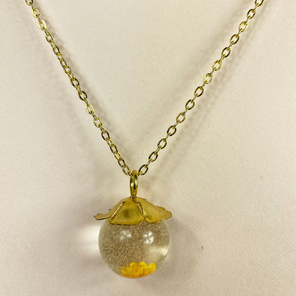 Medium view of necklace, showing the gold flower bead cap , the clear glittered orb and a peek at the yellow flower embedded at the bottom