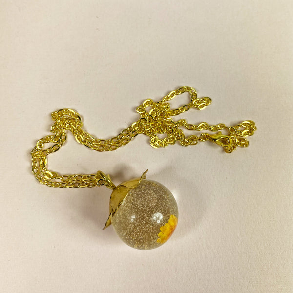 a side view of the necklace and its chain, showing the beautiful glittery quality of the resin sphere