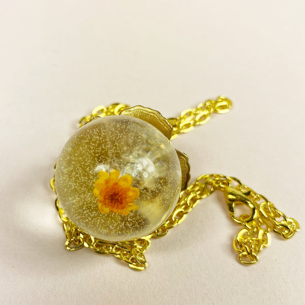 a close up view of the bottom of the orb, letting you see the sweet yellow flower embedded in the resin