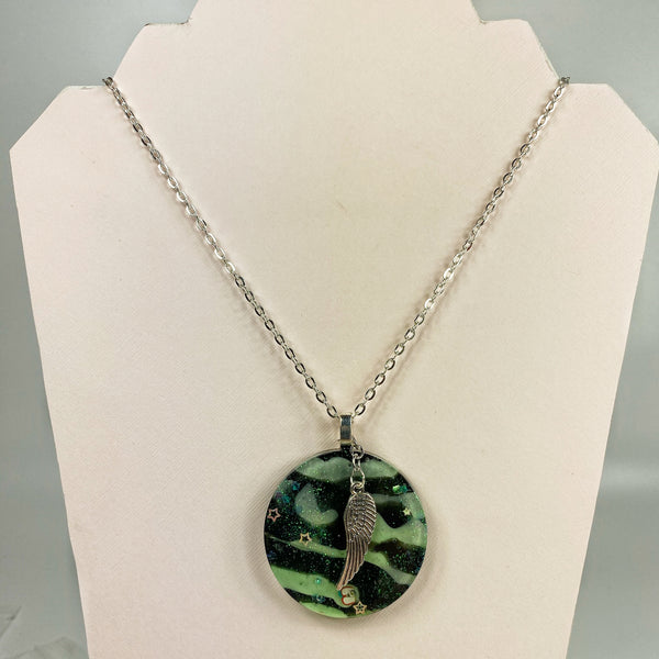 Green Tiger Striped Resin Necklace with Angel Wing shown on stand