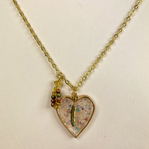 medium view of necklace showing pale pink translucent heart with multicolored glitter flakes