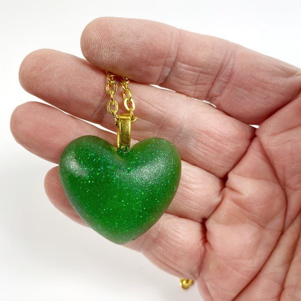 Lucky Green Heart Resin Necklace held in hand for size reference