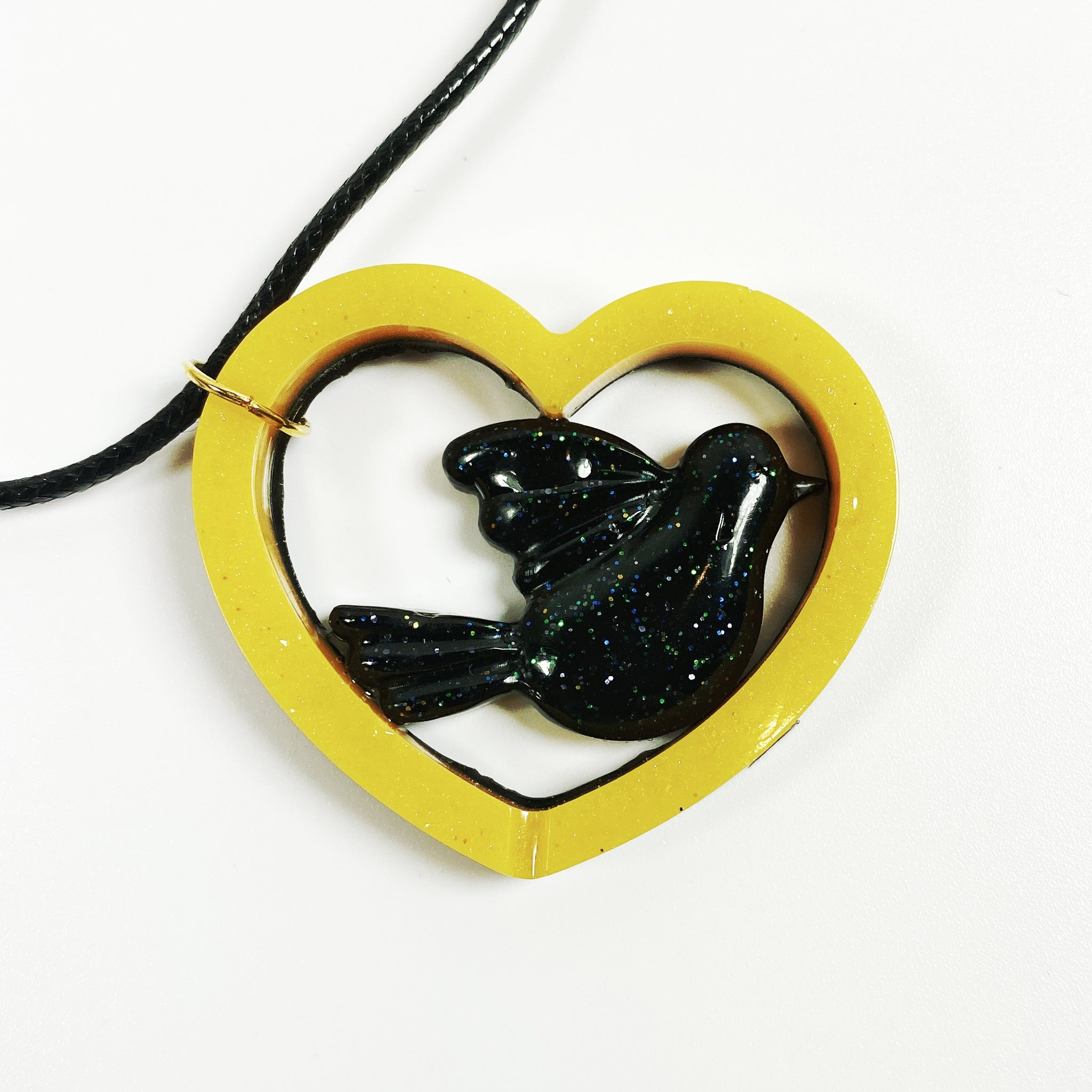 black dove in gold heart front view