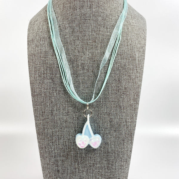 Pale Blue with White Cherries Glitter Resin Necklace on grey necklace stand
