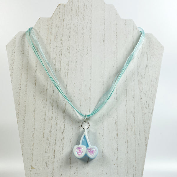 Pale Blue with White Cherries Glitter Resin Necklace on white wood necklace stand