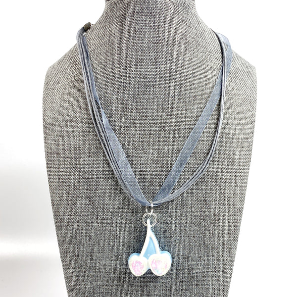 Iridescent White Cherries on Blue Resin Necklace on grey tween necklace display stand