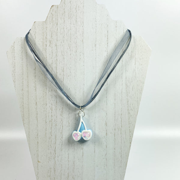 Iridescent White Cherries on Blue Resin Necklace on pale wood earring display stand