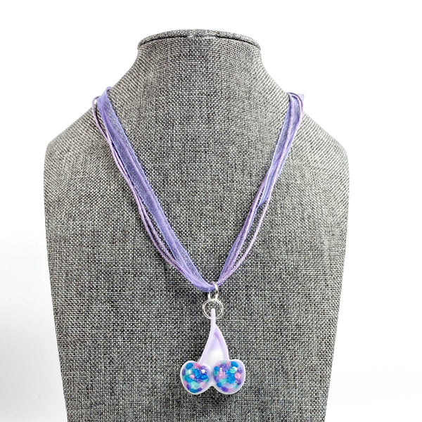 Blue Tutti-Frutti Cherries Resin Necklace on grey tweed necklace stand