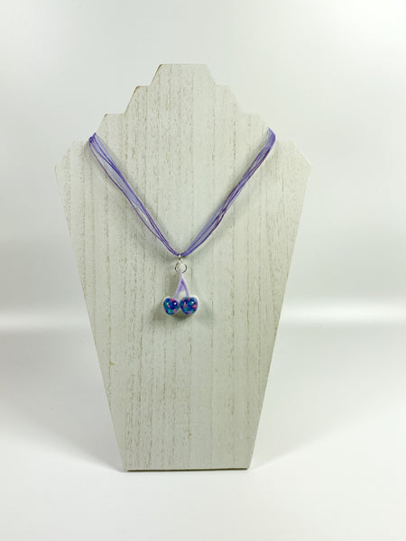Blue Tutti-Frutti Cherries Resin Necklace on pale wood necklace stand