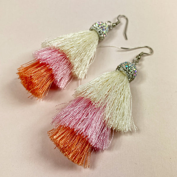 Full view of earrings, with cream, pink and coral layers of tassels