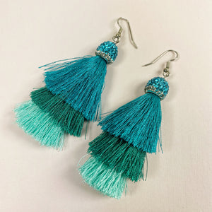 view of entire earring, rhinestone cap with three layers ocean-colored tassels