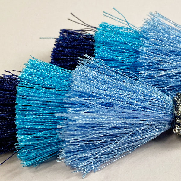 closeup of the lower part of these earrings, showing the luster of the tassel threads