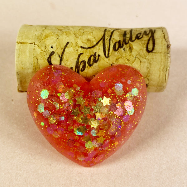 Starry heart pin with a wine cork for scale