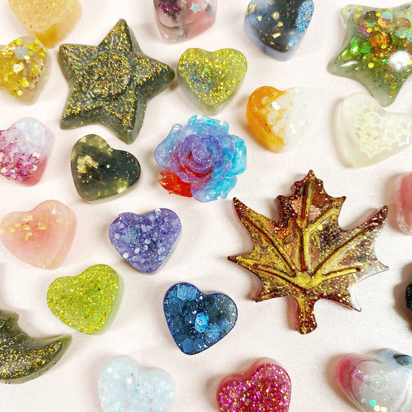 Half inch resin miniPins, mostly hearts but also a few random stars, flowers, leaves, moons