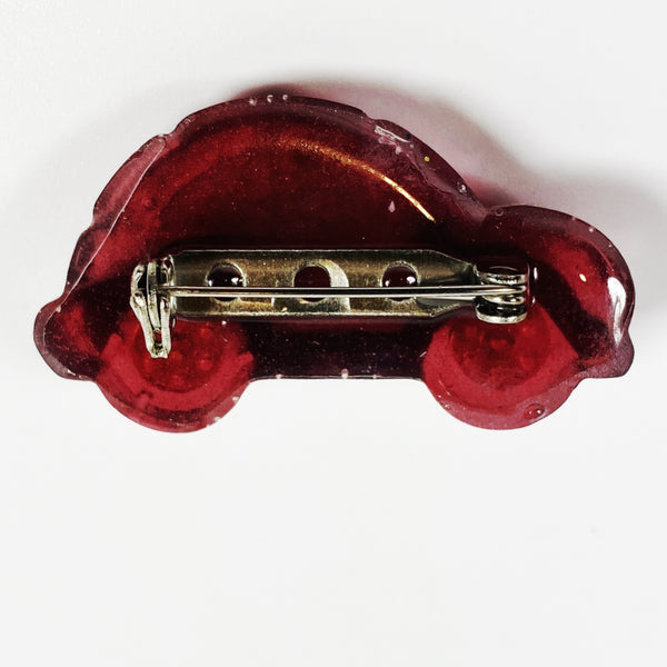 Red VW resin pin with ruby wheels, back  view showing clasp