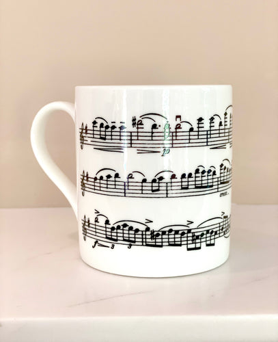 Music gift ideal for classical music fans. Elegant bone china mug with a section of Mendelssohn's Violin Concerto printed on in black. This fabulous mug is perfect for any violin player or music lover. A combination of a full capacity of 310ml and a subtle lip and classic handle design makes this mug both comfortable and stylish. Microwave and dishwasher safe. Height 85mm; Diameter 77mm. View from left thechord.co.uk