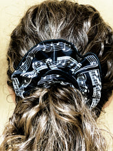 Load image into Gallery viewer, Musical hair tie scrunchie. White music score on black material.  Hand-made, large size (approx 15cm diameter). Shown on model.