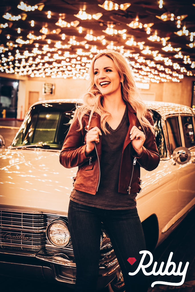beautiful blonde woman in leather coat by vintage car under neon lights in downtown Las Vegas