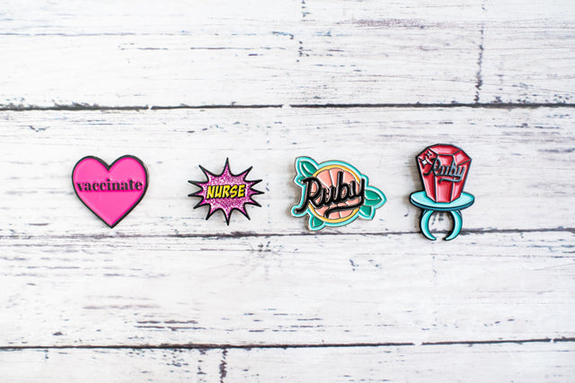colorful and fun enamel pins, hot pink, black, yellow, purple, glitter, aqua, green, yellow, peach, red, silver, white
