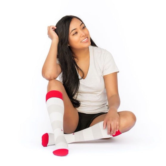 beautiful Indian woman in grey striped compression socks with red heel toe and cuff sitting