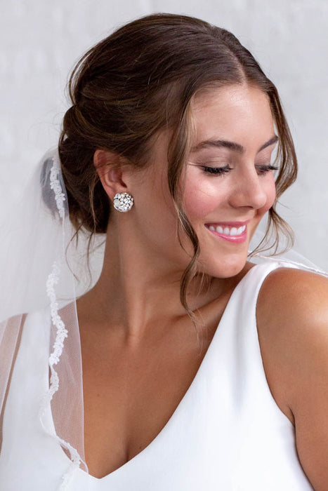 A smiling bride looking to her right. She is wearing a lace-edged veil and stud earrings along with her white wedding dress. The stud earrings include clusters of clear Swarovski crystals and diamond white pearls. Sara Gabriel