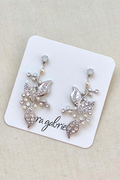 A bride is wearing a white dress and a leafy designed earring that uses a gold plated metal filigree as its base, incorporating the tiniest of Swarovski clear crystals and pale ivory pearls. This is dangled from a crystal post. Made by Sara Gabriel.