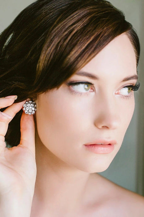 Closeup of a woman wearing sparkly bridal dome-shaped earring studs with clear Swarovski crystals being worn. Made by Sara Gabriel.