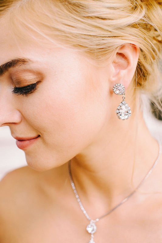 A bride showing off her sparkling silver drop earring made with clear Swarovski crystals and crystal-set chain. Made by Sara Gabriel.