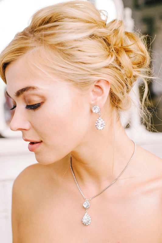 A bride wearing her sparkling teardrop pendant necklace using clear Swarovski crystals and crystal-set chain alongside her matching drop earrings made with Swarovski crystals and surrounded by crystal-set chain. Made by Sara Gabriel.