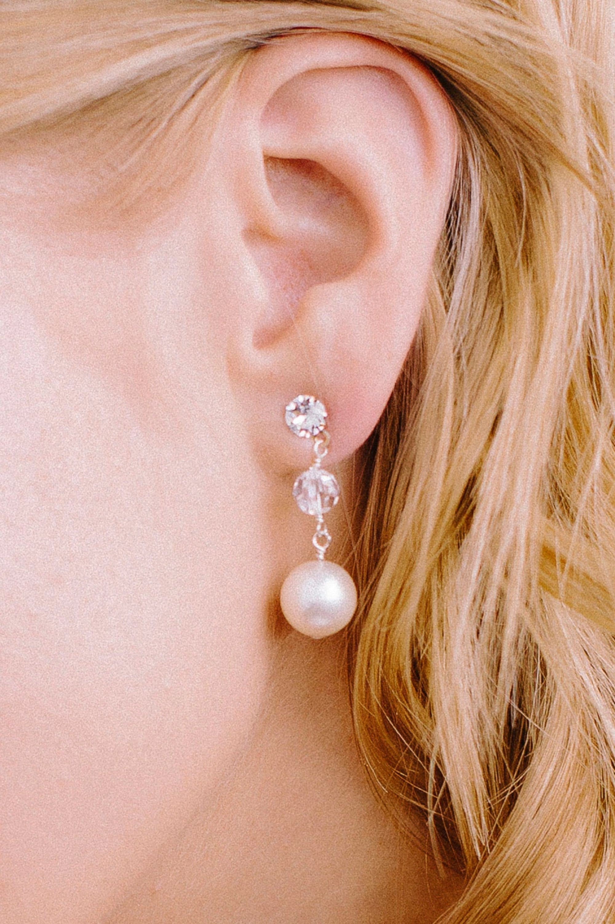A left, double drop earring that consists of a perfect pearl dropped from a clear crystal,  all dangling from a small, sparking crystal stud. Made by Sara Gabriel.