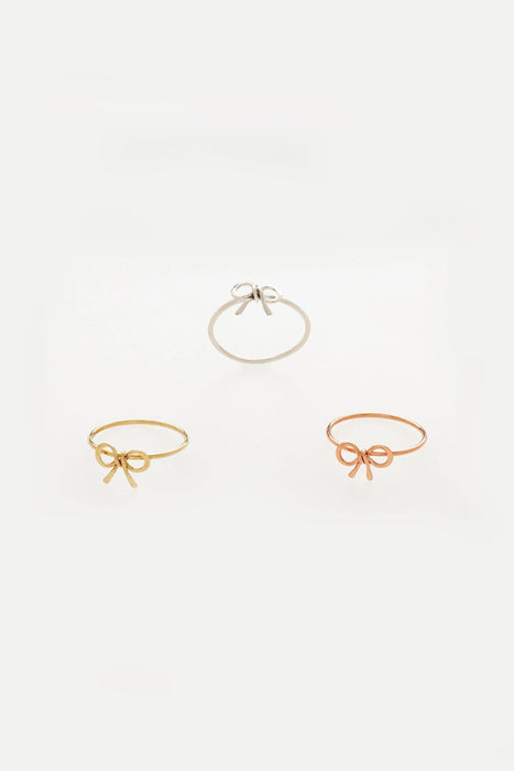 An array of three, identical shaped rings, plated in different colors. Those being silver, gold and rose gold. Sara Gabriel.