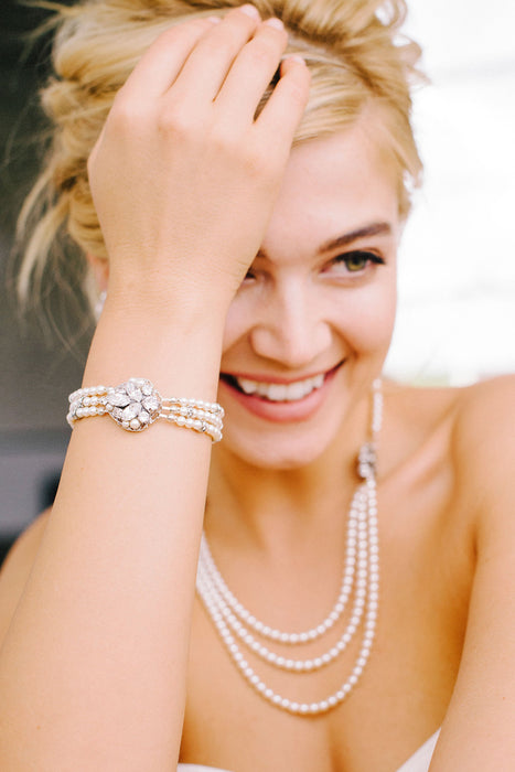 A smiling woman gazing off slightly to the left, wearing her three-strand Swarovski pearl and crystal bracelet joined together by a crystal and pearl encrusted filigree. She is also wearing a matching necklace made with Swarovski pearls and crystals. Sara Gabriel.