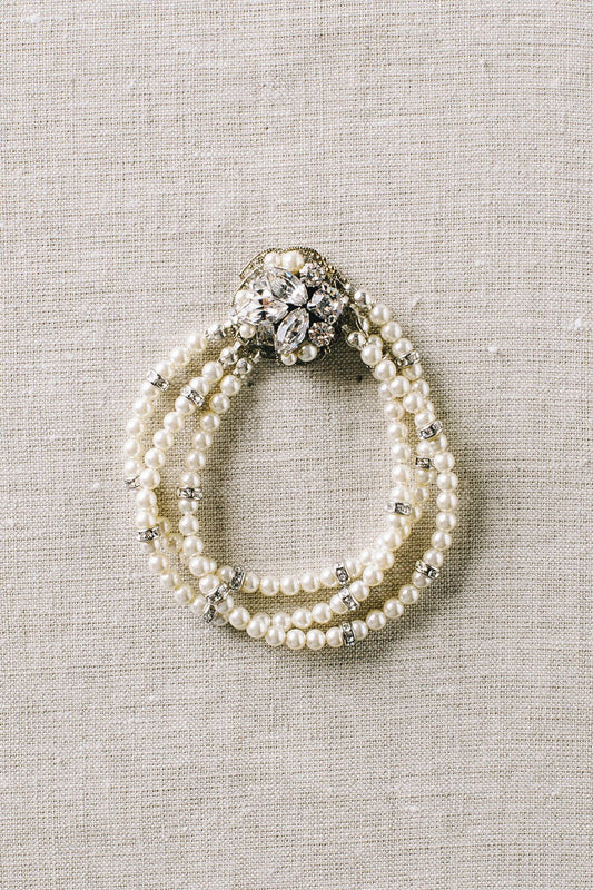 A three-stranded Swarovski pearl and crystal bracelet joined together a Swarovski crystal and pearl encrusted filigree that is hiding a magnetic clasp. Made by Sara Gabriel.