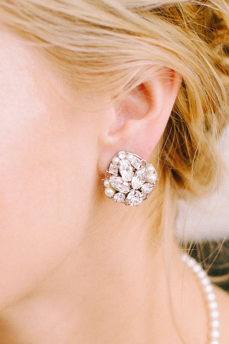 A zoomed in picture focusing on a single sparkly stud composed of clear Swarovski crystals and pale ivory pearls being worn. Made by Sara Gabriel.