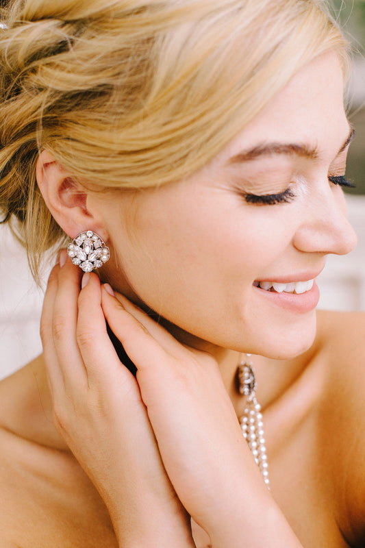 Eyes closed, smiling, a woman is wearing her stunning stud earrings that are made with Swarovski crystals and pearls to form a hand-set chic design all on a rhodium plated fiilgree. Made by Sara Gabriel.